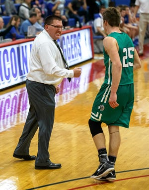 Athens basketball head coach Jeff Johnston celebrates with Athens' Drayton Davis after Davis created a turnover and made a shot that put the Warriors up 48-47 against Auburn in the second half during opening night of the 2018 Sangamon County Tournament.