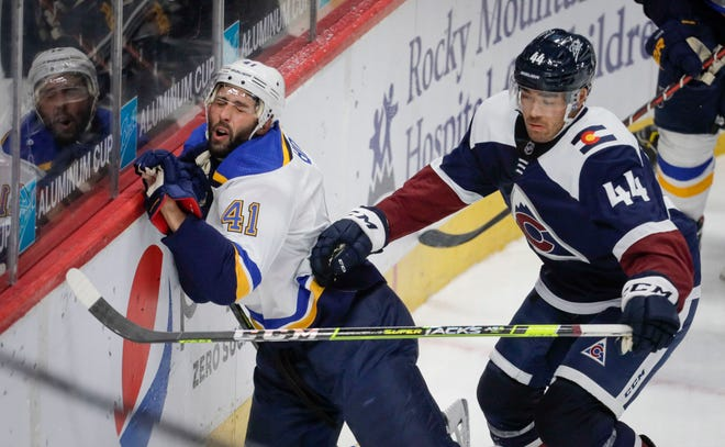 St. Louis Blues defenseman Robert Bortuzzo (41) hits the boards as Colorado Avalanche left wing Kiefer Sherwood (44) chases the puck in the third period in Denver, Friday, April 2, 2021.