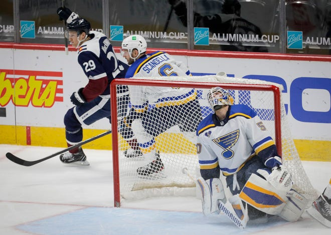 St. Louis Blues goaltender Jordan Binnington (50) reacts to a goal by Colorado Avalanche center Nathan MacKinnon (29) in the second period in Denver, Friday, April 2, 2021. Blues defenseman Marco Scandella (6) skates behind the goal.