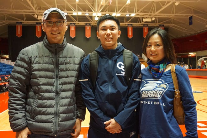 Georgia Southern basketball player Eito Yuminami, center, takes a photo with his parents following a game in the 2019 Sun Belt Tournament in New Orleans.