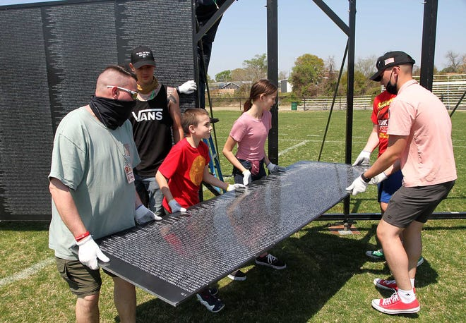 The Vietnam Veterans Memorial Replica Wall and Mobile Education Center is assembled by volunteers, exhibit staff, military veterans and US Marines from MCAS Cherry Point, at Lawson Creek Park in New Bern, NC, April 7, 2021. The Vietnam Veterans Memorial Replica Wall also known as The Wall That Heals, features a three-quarter scale replica of the Vietnam Veterans Memorial located in Washington, DC. The national exhibit honors the more than three million Americans who served in the US Armed Forces in the Vietnam War and it bears the names of the 58,279 men and women who died in Vietnam. The Vietnam Veterans Memorial Replica Wall and Mobile Education Center exhibit is open to the public at Lawson Creek Park, April 8-11, 2021. [Gray Whitley / Sun Journal Staff]