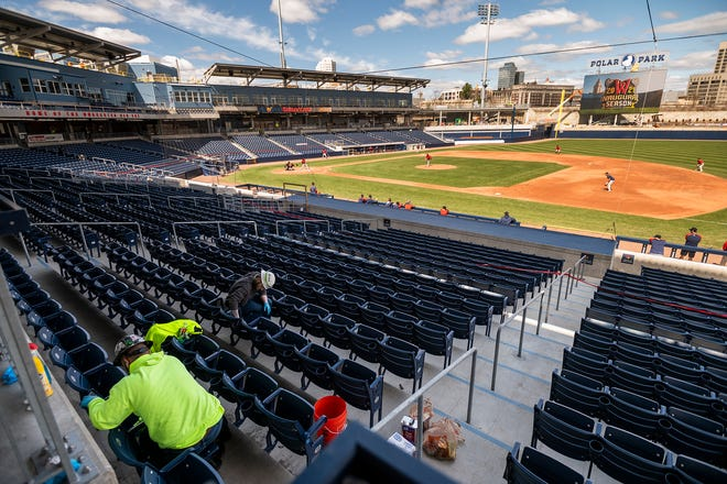 Workers clean the seats at Polar Park in Worcester as WooSox players get in a simulation game Wednesday.