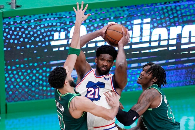 Philadelphia's Joel Embiid, center, looks to pass while pressured by Boston forward Jayson Tatum, left, and center Robert Williams III, right, during the first half of Tuesday's game.