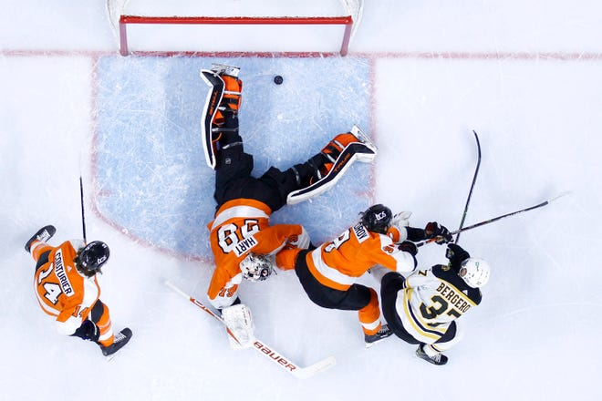 Boston's Patrice Bergeron, right, scores a goal past Philadelphia goaltender Carter Hart as Ivan Provorov (9) and Sean Couturier (14) defend during the first period of Tuesday's game.