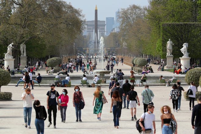 People walk in a path of the Tuileries garden in Paris on April 1.