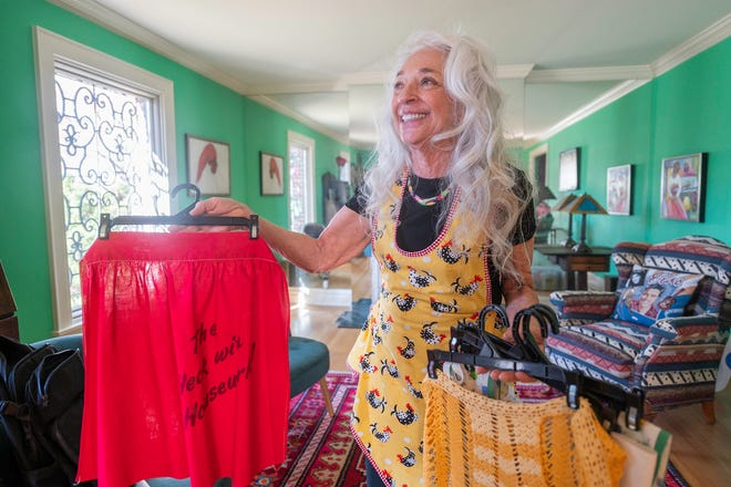 "EllynAnne Geisel holds some of the many aprons in her large collection earning her the nickname ""The Apron Lady""."