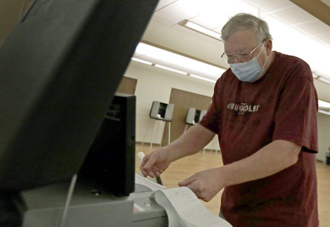 David Hoks of Appleton scans his ballot to complete his vote at Memorial Presbyterian Church.