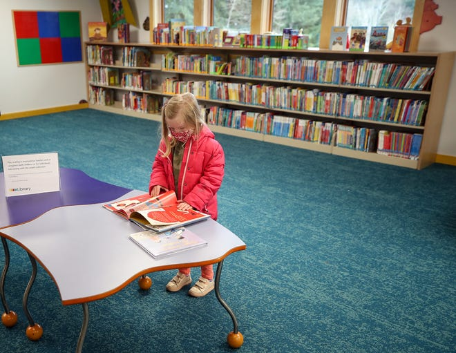 Campbell Neste, 3, flips through a book at a table in the children's section of the Kitsap Regional Library in Poulsbo on Wednesday, April 7, 2021.