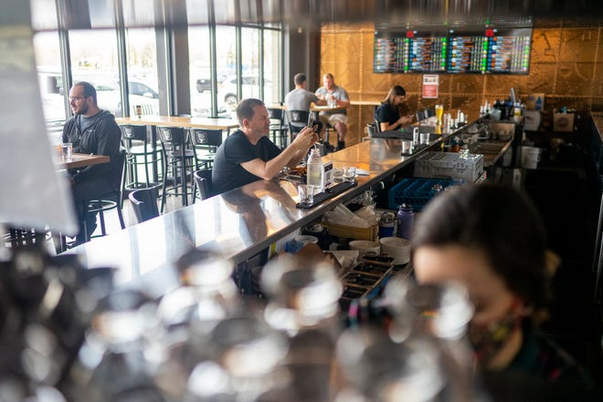 """People dine and drink at Brown Iron Brewhouse on Wednesday, April 7, 2021, in Royal Oak. The restaurant opened its second location in Royal Oak last March. """"The demand from customers is there,"""" Patti Eisenbraun, co-owner, said. """"We're ready."""""""