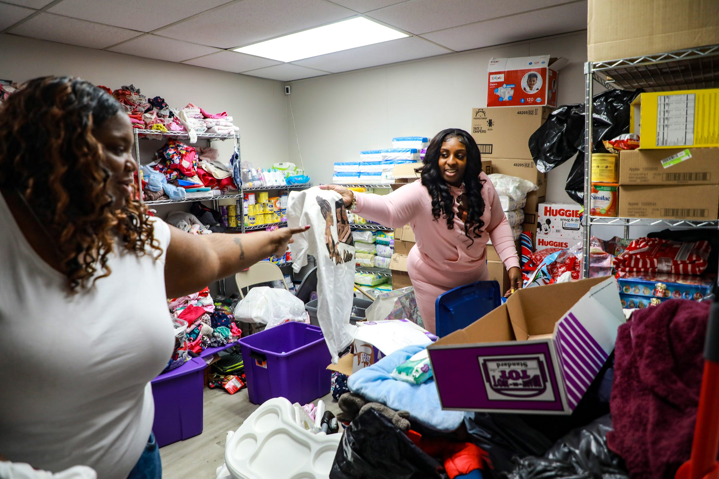 """Tyra Moore, founder of A Girl Like Me, Inc. non-profit, hands t-shirts to Shantell Woods, 32, of Detroit to hand out to the young girls in their mentorship class every Saturday in Southfield on March 13, 2021. Moore says the non-profit serves young girls and helps them navigate growing up with loss, stress and puberty. A Girl Like Me, Inc. also provides resources like food and baby items. """"We're like big sisters to them,"""" says Moore, """"if they don't have anyone to talk to, they can always talk to us about anything that may be going on in their life."""""""