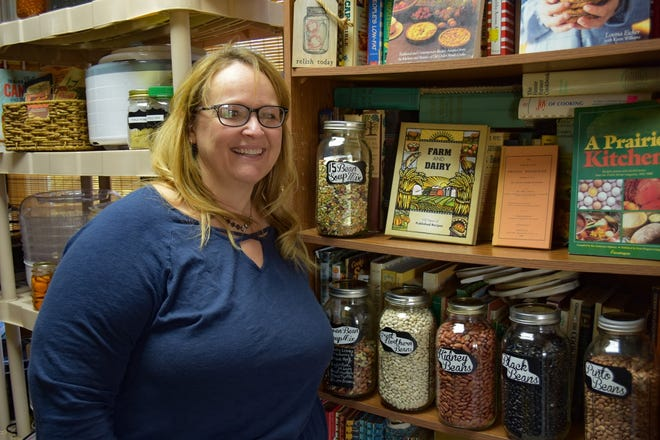 Toni Pendleton stands in her Lindsey home next to some of her many food preservation books and jars of dried beans. Behind her is her collection of dehydrators. Pendleton's passion for homesteading inspired her to start a local chapter of National Ladies Homestead Gathering.