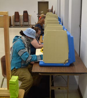 Several voters are seen marking their ballots at the Oconto Municipal Building on Tuesday, April 6.