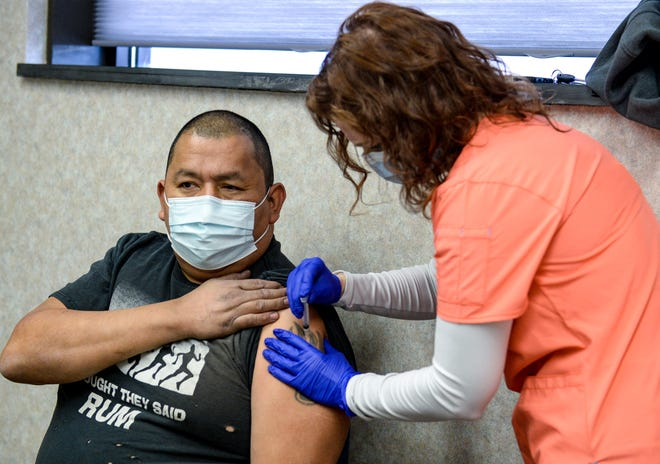 Chris Boy receives his COVID-19 vaccination from nurse Jessica Curtis at the Indian Family Health Clinic on Wednesday, April 7, 2021.