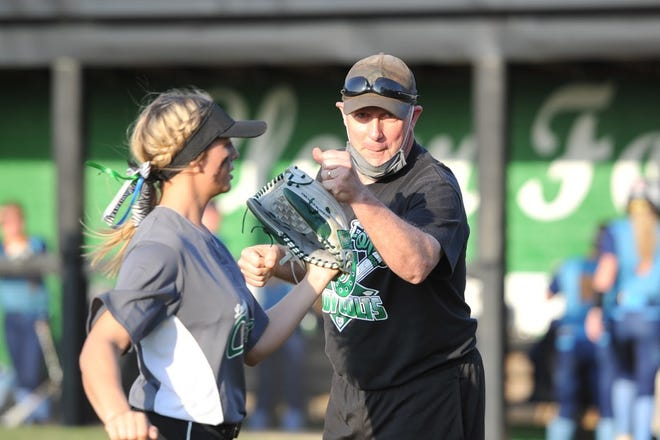 Clear Fork softball coach Jeff Gottfried fist bumps centerfielder Pacey Chrastina during a game this season sporting his signature hat that has seen some of the most incredible moments in Clear Fork softball history.