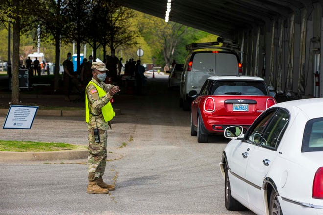 National Guard soldiers direct people to vaccination areas near the Pipkin Building  in Memphis on Wednesday, April 7, 2021.