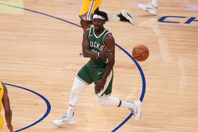 Milwaukee Bucks guard Jrue Holiday delivers a no-look pass in the first half Tuesday night. Holiday led the Bucks with 29 points.