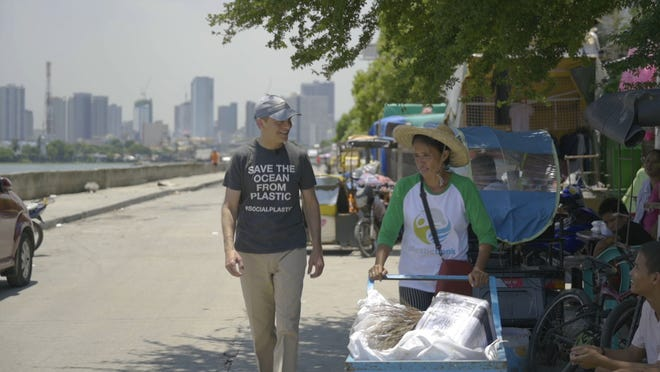 Fisk Johnson, chairman and CEO of SC Johnson, walks with a woman wearing a Plastic Bank shirt. SC Johnson and Plastic Bank have partnered to remove plastic from the world's oceans.