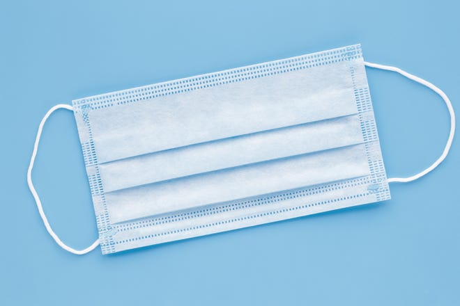 Surgical mask with rubber ear straps. Typical 3-ply surgical mask to cover the mouth and nose. Procedure mask from bacteria. Protection concept