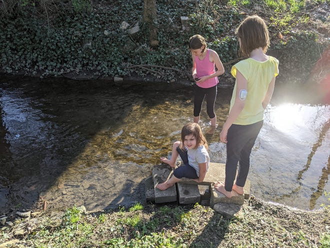 The Roy daughters play in a creek. Recently Bookworm, in pink, helped The Architect, in yellow, share her type 1 diabetes diagnosis with her classmates.