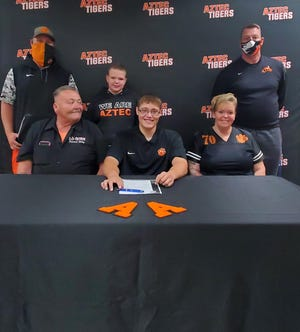 Aztec's John Taigaafi signs his National Letter of Intent on Wednesday, April 7, 2021, to continue his football career at NAIA Clarke University.