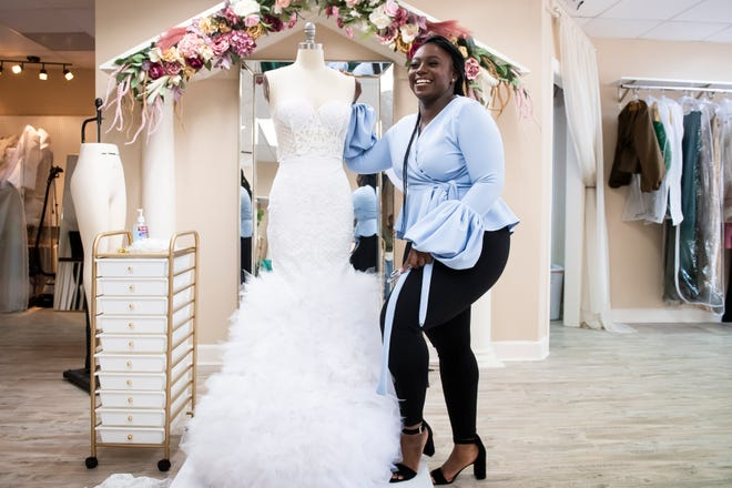 Symone Gaither poses for a photo next to one of the bridal dresses she is creating at her newly-opened bridal and evening wear shop, Amelia Symone, in downtown Hanover.