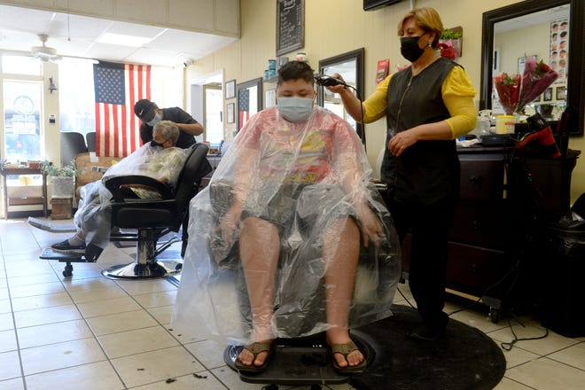 Santiago Hernandez, 11, gets his hair cut by Rosie Zamora, a stylist at Godinez Barbershop in Santa Paula, on Wednesday, April 7, 2021. Ventura County moved into the less restrictive orange tier allowing businesses to open up more.