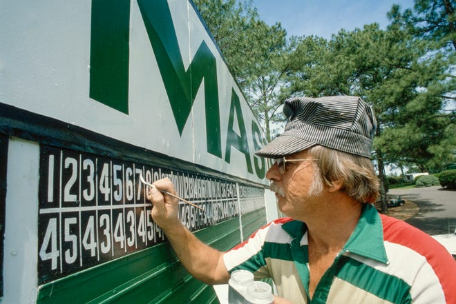 A worker touches up the 1981 Masters scoreboard at the Augusta National Golf Club.