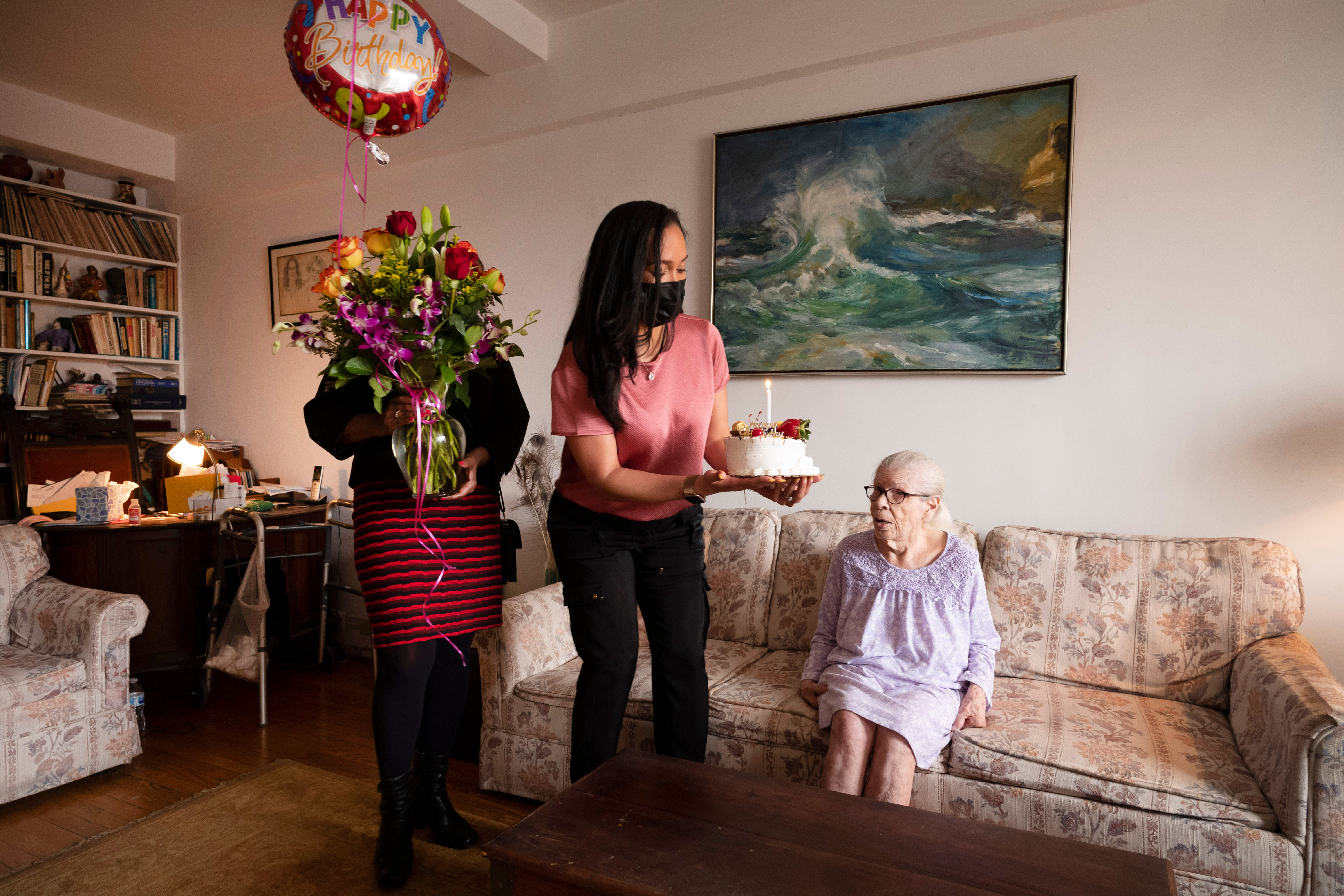 Dolores McGinnis, left, carries flowers, and her co-worker Stacy Munoz-Laporte brings a birthday cake for Josephine Melecio as she celebrates her 110th birthday, Friday, March 26, 2021, in New York. McGinnis and Munoz-Laporte are nurse care managers with RiverSpring Health, a long-term care program that assists the elderly in living independently at home.
