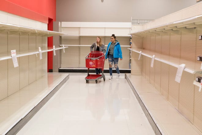 Two women walk through empty toilet paper aisles at Target in March 2020. This household necessity was hard to find during March, April and even May of 2020. The shortage was largely caused by consumers over- and panic-buying while predicting a long-term lockdown.