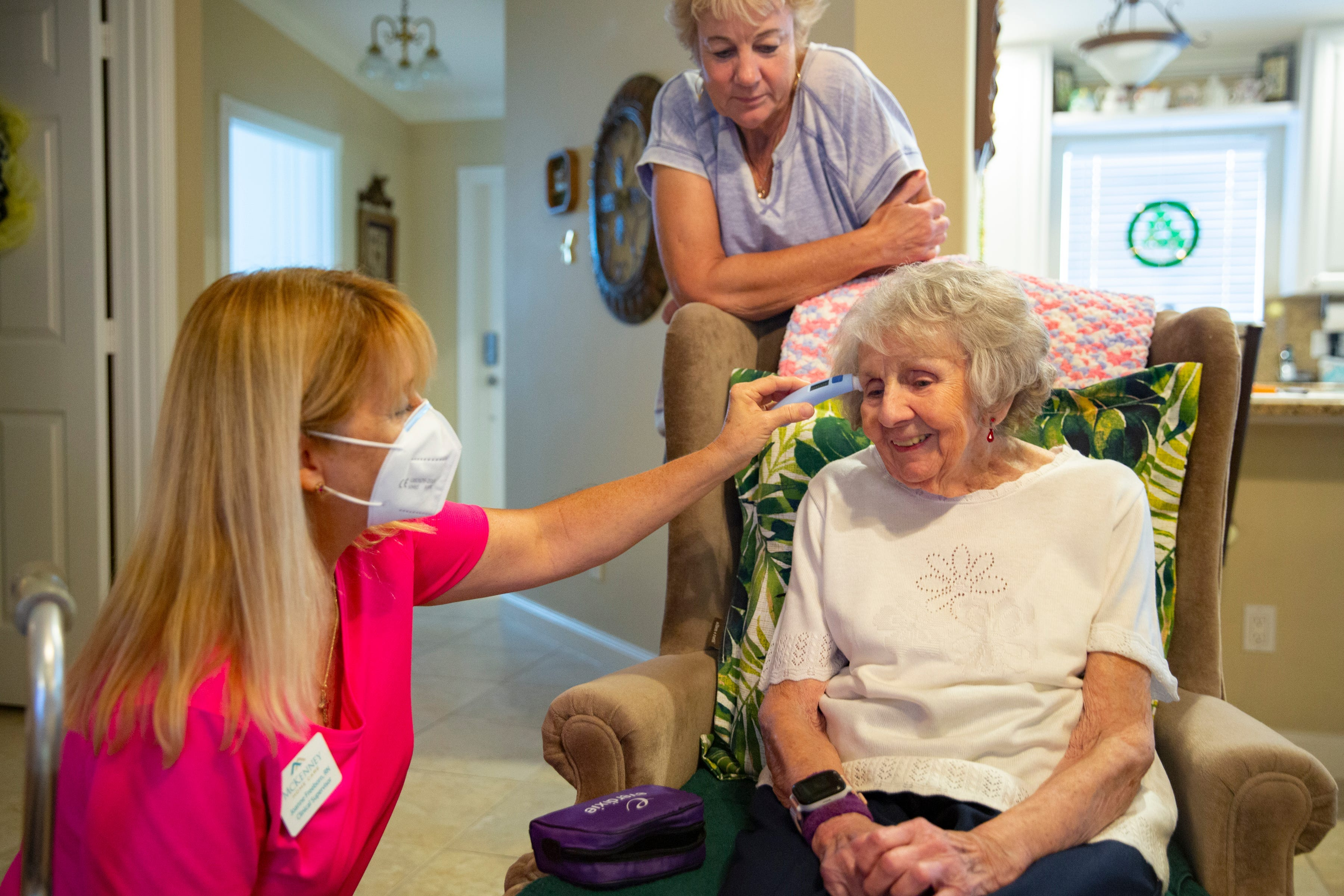 Registered nurse Joanne Freeborn, left, checks the temperature of Mary Jo Smith's mother, Jean Murphy, in October at their home in East Naples, Fla.