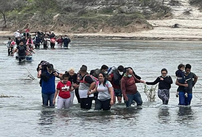 Migrants crossing the Rio Grande into Texas being rounded up by Val Verde County Sheriff deputies in April 2021.