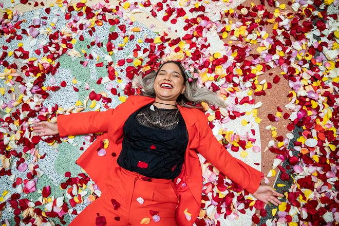 Tori Baltierra moves her arms to make an angel among fallen rose petals at the Capitol on Thursday. Members of the advocacy groups Jolt and NextGen tossed 270,000 rose petals in the Capitol rotunda to represent the over quarter of a million Texans of color who turn 18 every year. The groups aim to boost the civic participation of Texans of color.