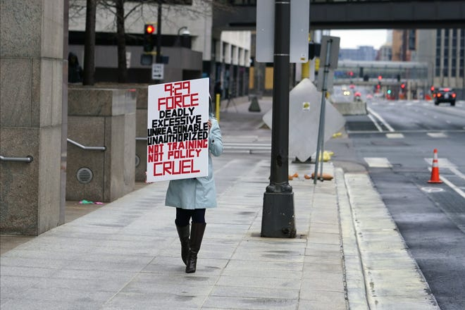 A protester carries a sign across the street from the Hennepin County Government Center, Thursday in Minneapolis where testimony continues in the trial of former Minneapolis police officer Derek Chauvin. Chauvin is charged with murder in the death of George Floyd last May. [AP PHOTO/JIM MONE]