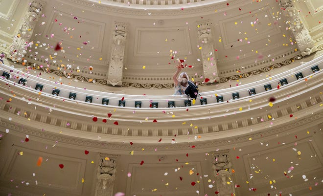 Rose petals rain down inside the Capitol rotunda on Thursday. The 270,000 rose petals were meant to represent the Texans of color who turn 18 every year and become eligible to vote.