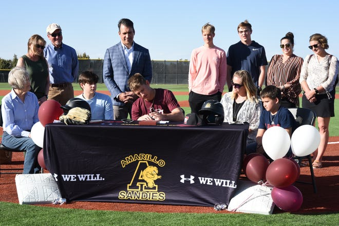 Max Milligan, center, signs his letter of commitment to Trinity University at Sandie Baseball Field on Thursday.