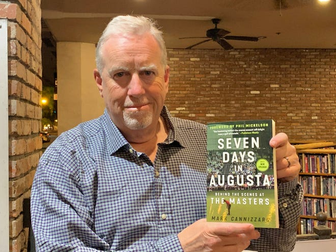 """Writer and journalist Mark Cannizzaro shows off his book """"Seven Days in Augusta: Behind the Scenes at the Masters"""" during a book signing Wednesday at The Book Tavern on Broad Street."""
