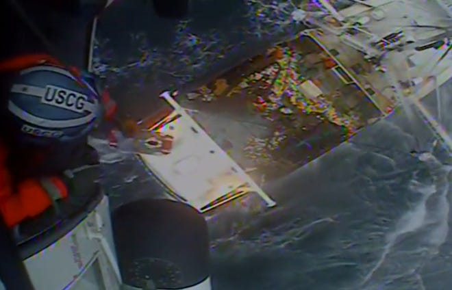 A Coast Guard helicopter hoists a crew member off a fishing boat about 113 miles southeast of Cape Cod on Wednesday.