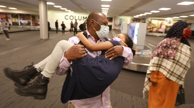 Mohamed Salem Ali twirls his granddaughter Reem, 6, shortly after he arrived at John Glenn International Airport. Ali, a Somali man, wasn't able to join his family in Columbus due to former President Donald Trump's Muslim ban. When Biden lifted the ban earlier this year, the family got their father a visa and he arrived in Columbus last week. At right is his wife, Fadumo Hussein.