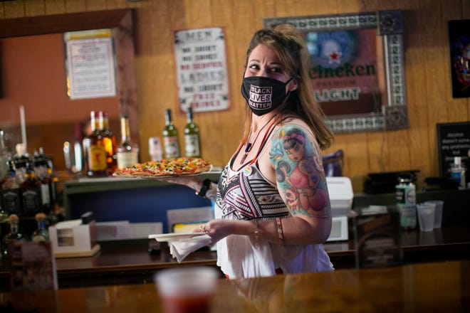 Bartender Kristen Zeune takes a pizza out to a patron at Slammers, one of only 15 lesbian bars in the country, and the only one in Ohio, according to a recent report.