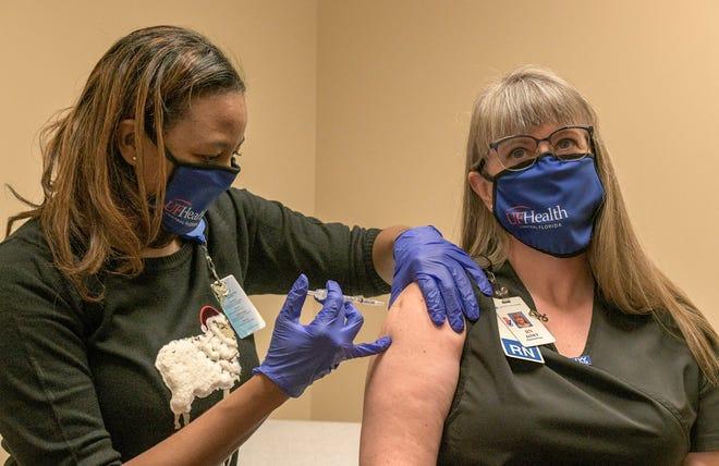 Pharmacist Erika Jasper gives nurse Janet Bennett a dose of the COVID-19 vaccine at UF Health Leesburg Hospital Urgent Care in Leesburg. [PAUL RYAN / CORRESPONDENT]