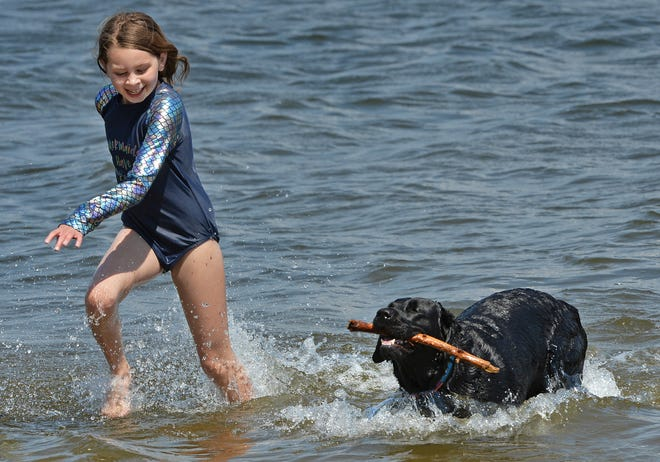 Eight-year-old Alexis Thomas plays with Hope, a four-year-old Labrador retriever owned by a neighbor, on April 8, 2021, at Edinboro Lake in Edinboro. Thomas was there with her mother and siblings. The temperature was 81 degrees at the time, eclipsing the old record for the day, 78 degrees set in 2001.