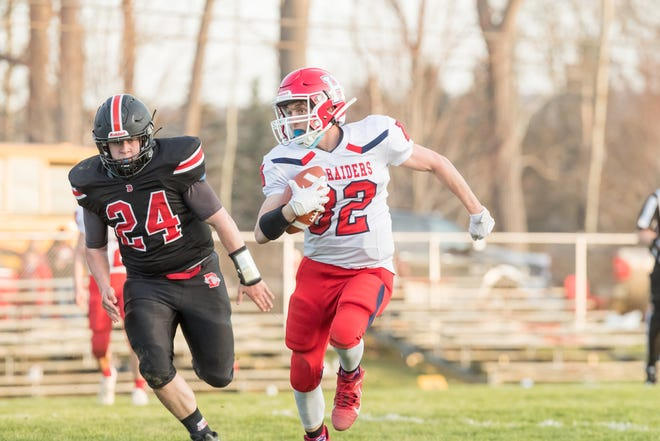Hornell's Mason Drew (32) races toward the edge as Dansville's Aidan O'Connor (24) chases after him.