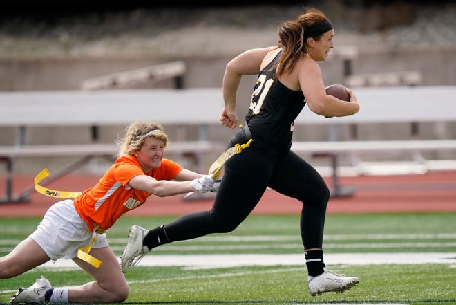 Ottawa quarterback Madysen Carrera (21) is tackled by Midland defender Casey Thompson, left, during an NAIA flag football game in Ottawa, Kan., on March 26. The National Association of Intercollegiate Athletics introduced women's flag football as an emerging sport this spring.