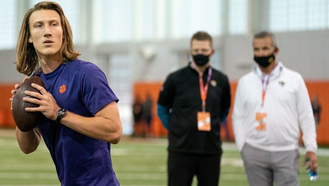 Clemson quarterback Trevor Lawrence works out as Jacksonville Jaguars head coach Urban Meyer (right) looks on in February.