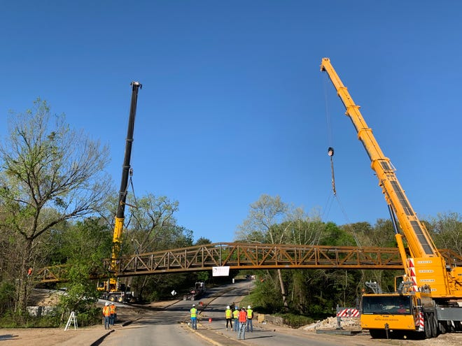 Crews in Denison work to place the Katy Trail bridge along Loy Lake Road Thursday morning. The bridge is a part of the city's new shared-use trail system that follows a former railroad right-of-way.