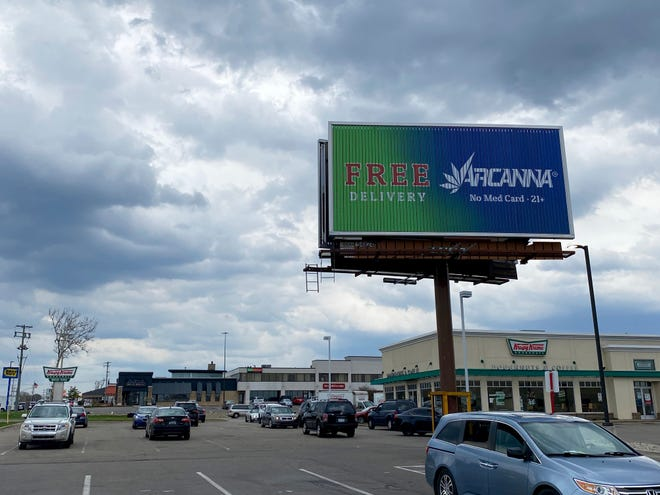A billboard for Arcanna, an Ionia-based recreational marijuana dispensary, is seen on display near the intersection of 28th Street and East Beltline Avenue in Kentwood, Mich., Thursday, April 8, 2021. Lawmakers in the Michigan Legislature plan on introducing bills to ban such billboards in the state. (Arpan Lobo/Sentinel Staff)