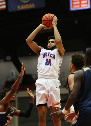 Hutchinson's Matt Mayers (21) shoots past Independence's Carsimir Paul (20) during the Region VI quarterfinal game at the Sports Arena Wednesday evening. Mayers scored 26 points in the game. Hutchinson won 93-74.