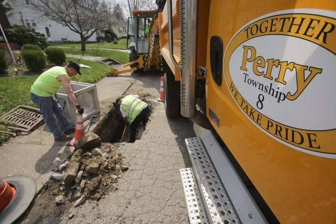 Perry Township Road Department workers Mark Johnson (left), John Smith (center), and Rob Halter (operating equipment) work Wednesday to install a new catch basin within the 300 block of Linway Avenue NW. The township plans to resurface sections of 15 northwest-area streets for its 2021 repaving initiative.