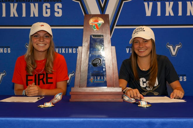 Lakeland Christian seniors Ramsey Watkins and Katie Carnes pose after with the state championship trophy at their college signing ceremony on Wednesday. Watkins signed with Southeastern, and Carnes signed with Charleston Southern.