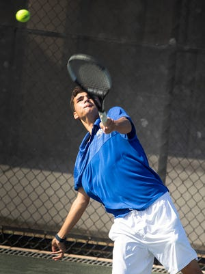 Winter Haven Nicholas Lopez  serves during a doubles match during the East County Tennis Tournament Winter Haven City Courts in Winter Haven Fl. Monday April 5 2021. ERNST PETERS/ THE LEDGER
